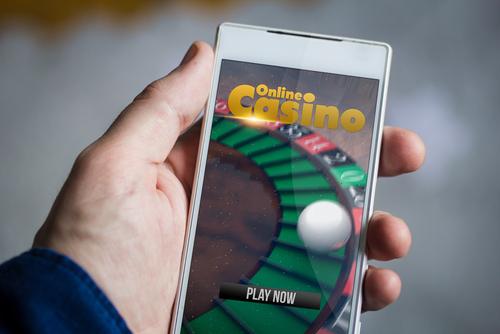 main masculine tenant un smartphone sur lequel apparait un jeu de casino en ligne