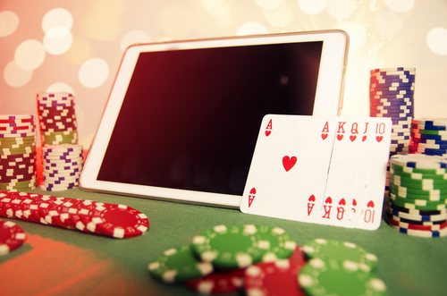 concept de poker en ligne avec une tablette, une quinte flush royale et une pile de jeton de casino